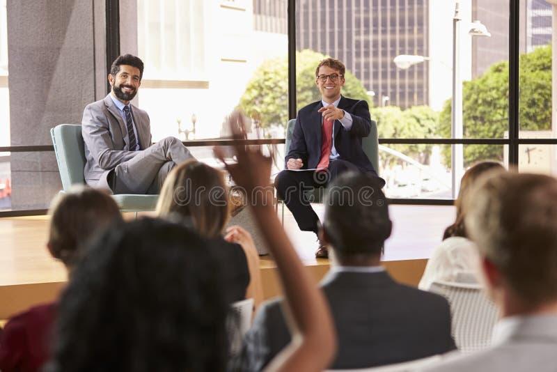 Gli altoparlanti ad un seminario di affari prendono le domande del pubblico fotografia stock