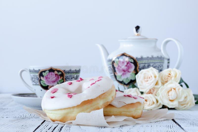 Gli amanti fanno colazione per il giorno di biglietti di S. Valentino con il tè e le rose rosse della ciambella fotografia stock libera da diritti