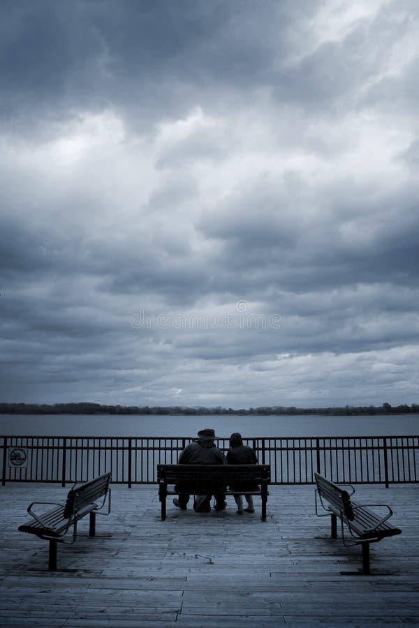 Gli amanti si siedono su un banco fotografie stock