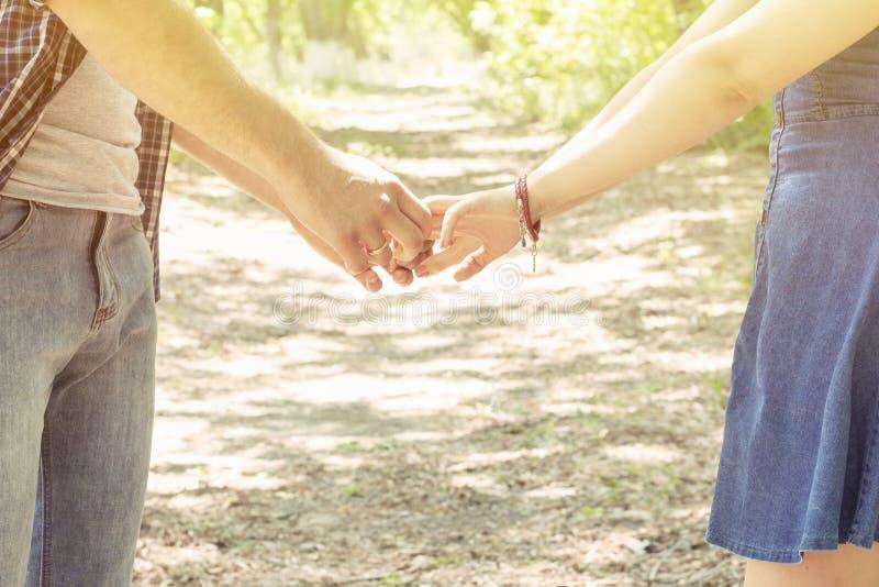 Gli amanti si tengono per mano giorno di estate soleggiato del supporto del ragazzo e della ragazza delle coppie immagine stock libera da diritti