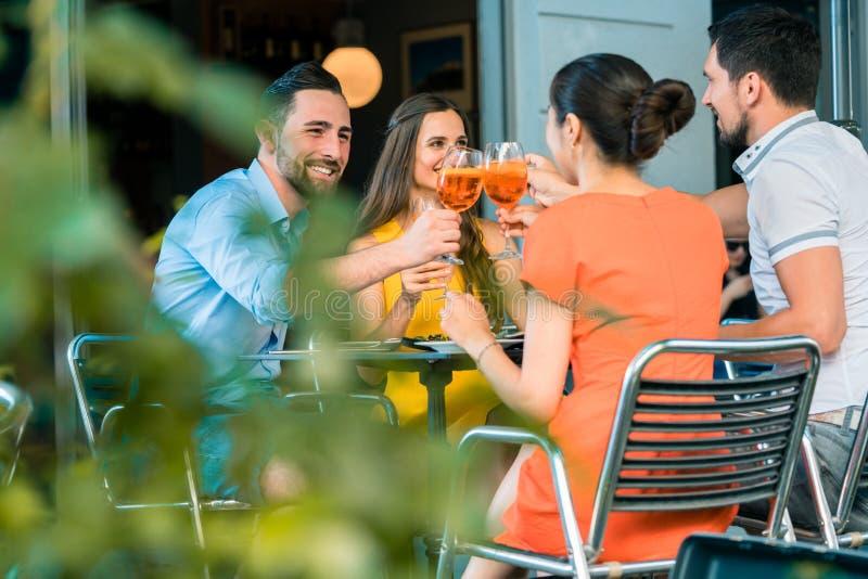 Gli amici allegri che tostano con un'estate di rinfresco bevono immagini stock libere da diritti