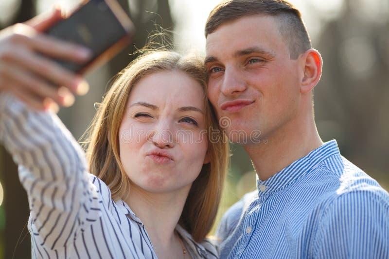 Gli amici allegri fanno il selfie e fare smorfie divertendosi mentre passeggiata fotografia stock libera da diritti