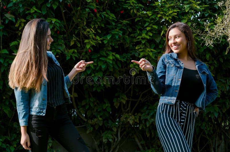Gli amici allegri stanno pettegolando nel parco Le ragazze stanno indicando con il loro dito e risata fotografia stock