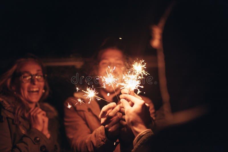 Gli amici che accendono il fuoco scintilla alla notte fotografie stock libere da diritti