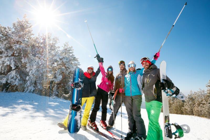 Gli amici che godono nella bella neve naturale abbelliscono sulla montagna immagini stock libere da diritti