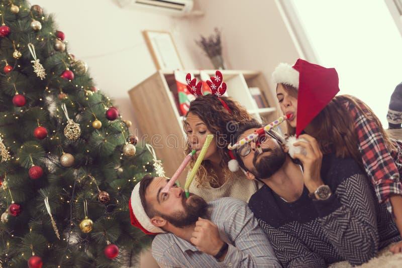 Gli amici che soffiano il partito fischia sul giorno di Natale fotografia stock libera da diritti