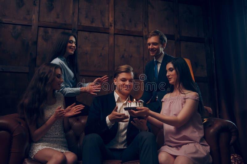 Gli amici danno ad un compleanno huy una piccola torta di compleanno immagini stock