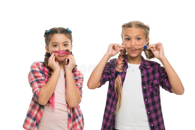 Gli amici di ragazze indossano le simili attrezzature hanno stessa acconciatura intreccia il fondo bianco Sorelle sguardo della f fotografia stock libera da diritti