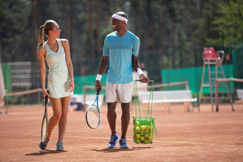 Gli amici di risata stanno andando giocar a tennise insieme all'aperto immagine stock libera da diritti