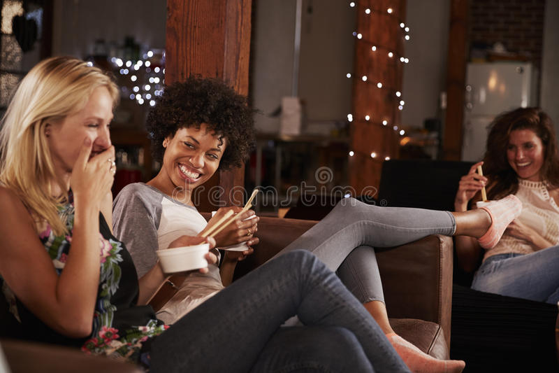 Gli amici dividono uno scherzo e un alimento di cinese ad una notte del ½ s del ¿ del girlï dentro fotografia stock libera da diritti
