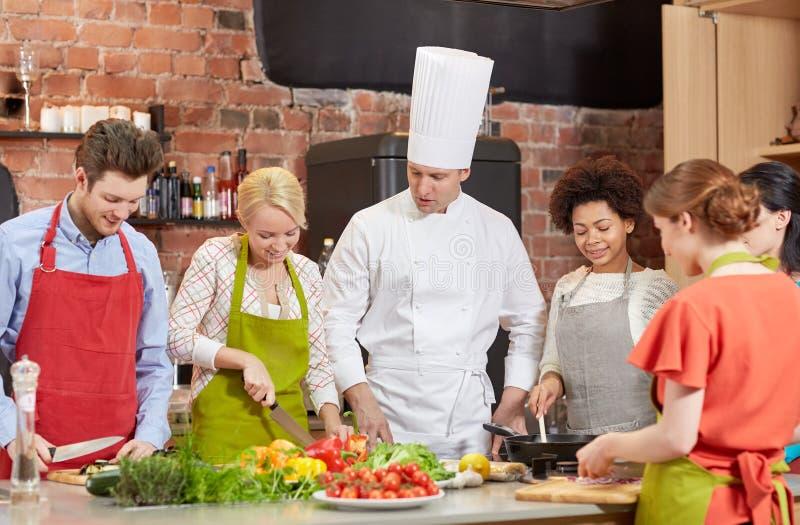 Gli amici ed il cuoco unico felici cucinano la cottura nella cucina fotografia stock
