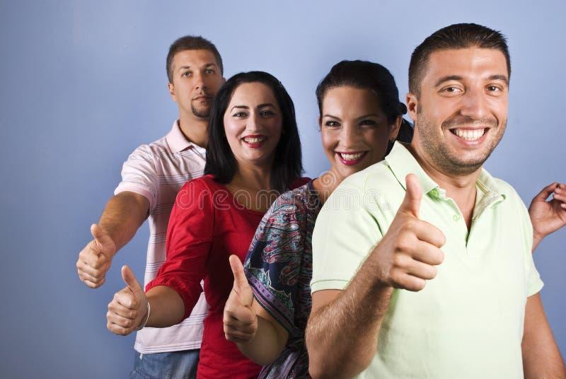 Gli amici felici danno i pollici in su in una riga fotografia stock