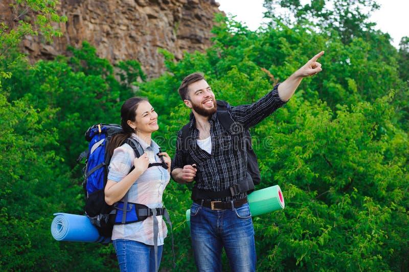 Gli amici felici nel fondo del cielo blu e dell'erba, si rilassano il tempo in vacanza, viaggio di concetto fotografia stock libera da diritti