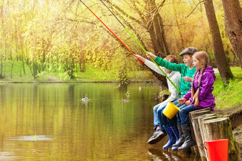 Gli amici felici si siedono la pesca insieme vicino allo stagno fotografia stock