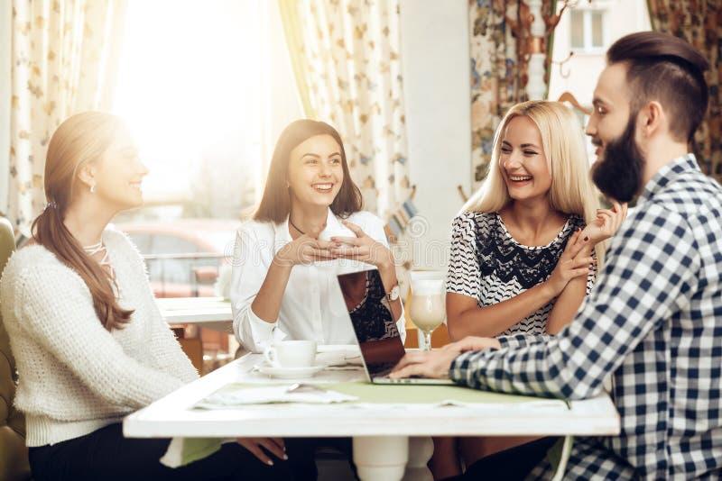 Gli amici felici stanno riposando in caffè bevente del caffè immagine stock libera da diritti