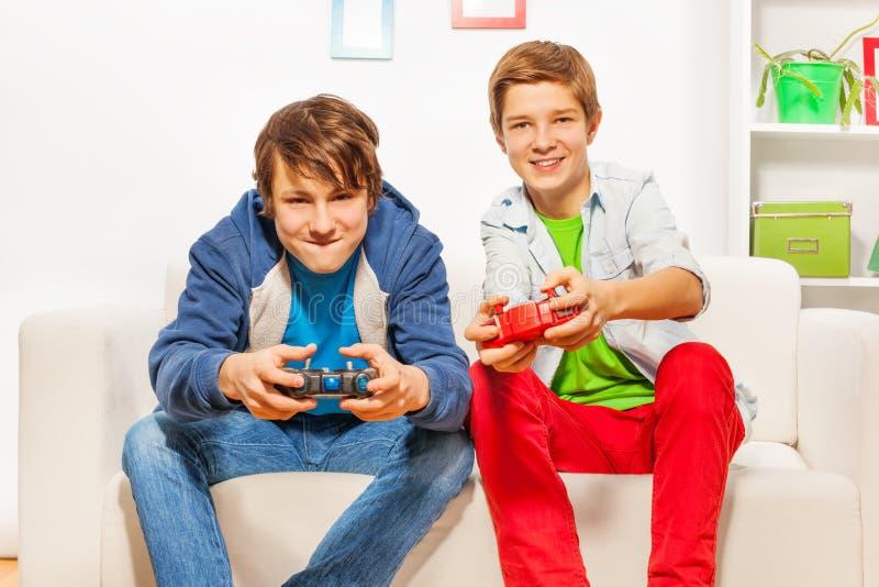 Gli amici felici tengono le leve di comando e la console del gioco del gioco immagine stock libera da diritti