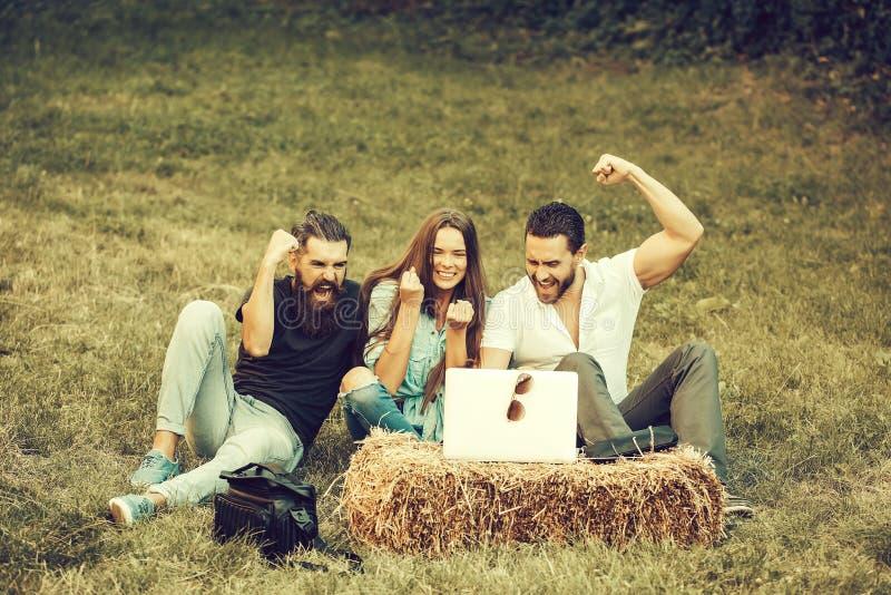 Gli amici felici utilizzano il computer portatile fotografia stock libera da diritti