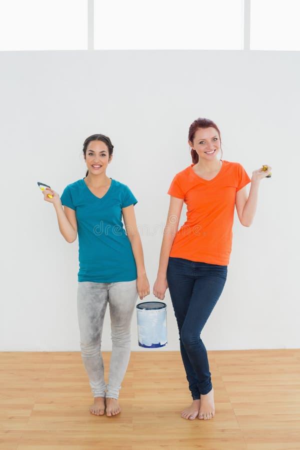 Gli amici femminili sorridenti con le spazzole e la pittura possono in nuova casa fotografie stock libere da diritti