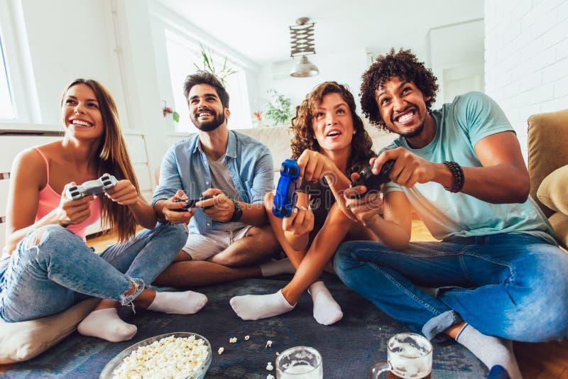 Gli amici giocano insieme i video giochi a casa, divertendosi fotografia stock libera da diritti