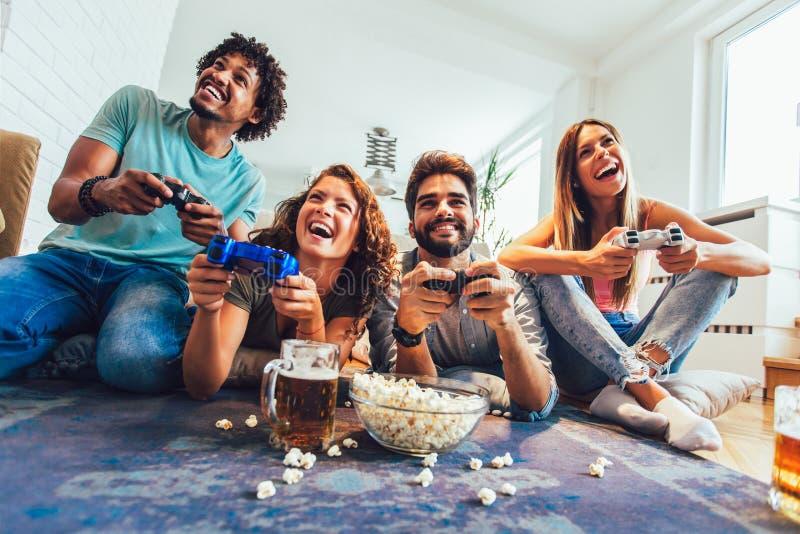 Gli amici giocano insieme i video giochi a casa, divertendosi fotografie stock libere da diritti