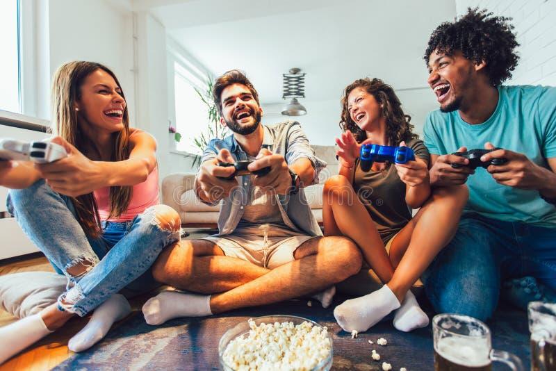 Gli amici giocano insieme i video giochi a casa, divertendosi fotografie stock