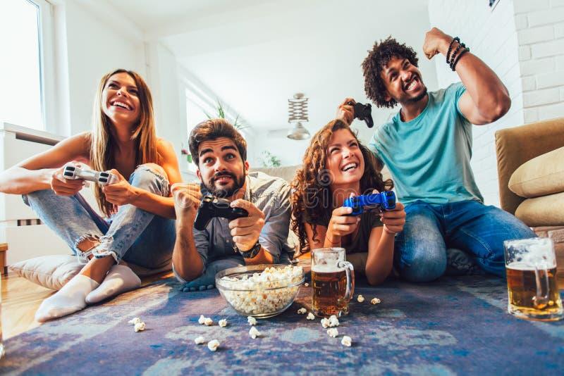 Gli amici giocano insieme i video giochi a casa, divertendosi fotografia stock