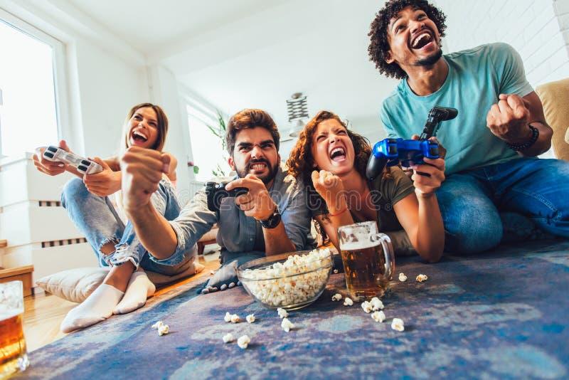 Gli amici giocano insieme i video giochi a casa, divertendosi immagini stock libere da diritti