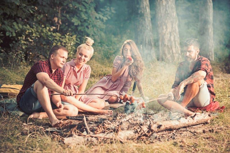 ( Gli amici hanno picnic al falò negli uomini della foresta e le donne arrostiscono le salsiccie su fuoco fotografia stock