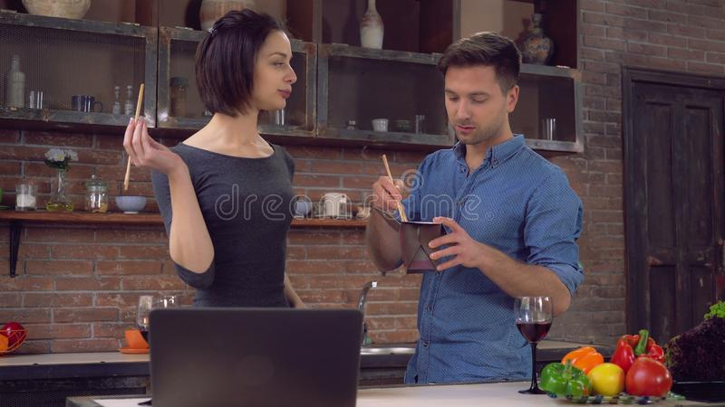 Gli amici mangiano le tagliatelle asiatiche con le verdure a casa immagini stock libere da diritti