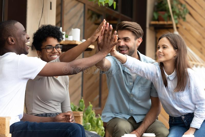Gli amici multietnici felici che danno su cinque, celebrano il successo immagini stock