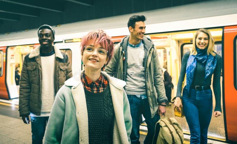 Gli amici multirazziali dei pantaloni a vita bassa raggruppano la camminata alla stazione della metropolitana del tubo immagini stock