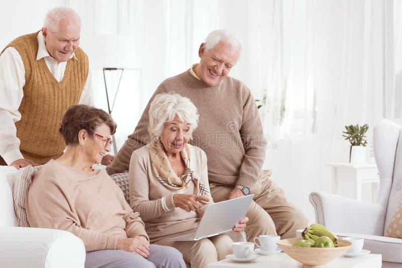 Gli amici più anziani stanno utilizzando il computer portatile immagine stock