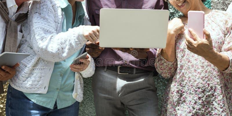 Gli amici senior si rilassano lo stile di vita facendo uso del concetto del dispositivo di Digital immagine stock