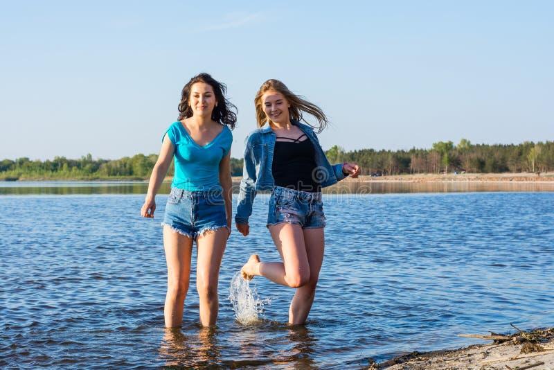 Gli amici stanno ballando e spruzzano l'acqua su una spiaggia, ridente La TW fotografia stock libera da diritti