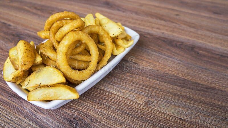 Gli anelli di cipolla sono servito su un piatto bianco, prodotti degli alimenti a rapida preparazione come sopra fotografia stock libera da diritti