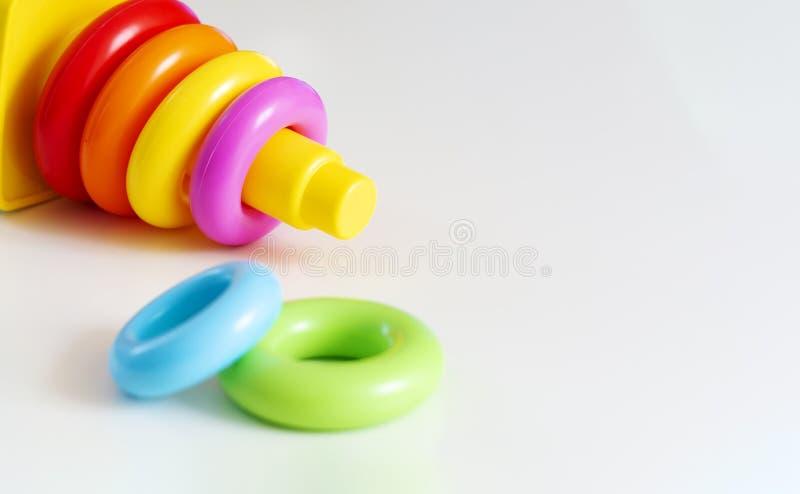 Gli anelli di plastica di vari colori sono impilati in una torre di plastica gialla fotografia stock