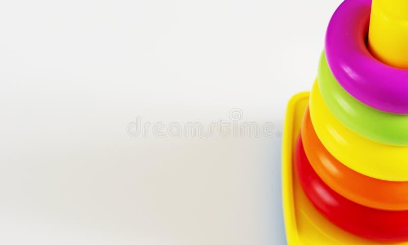Gli anelli di plastica di vari colori sono impilati in una torre di plastica gialla immagine stock