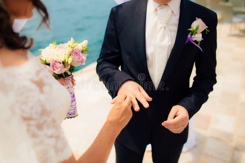 Gli anelli di scambio delle persone appena sposate alle nozze fotografia stock libera da diritti