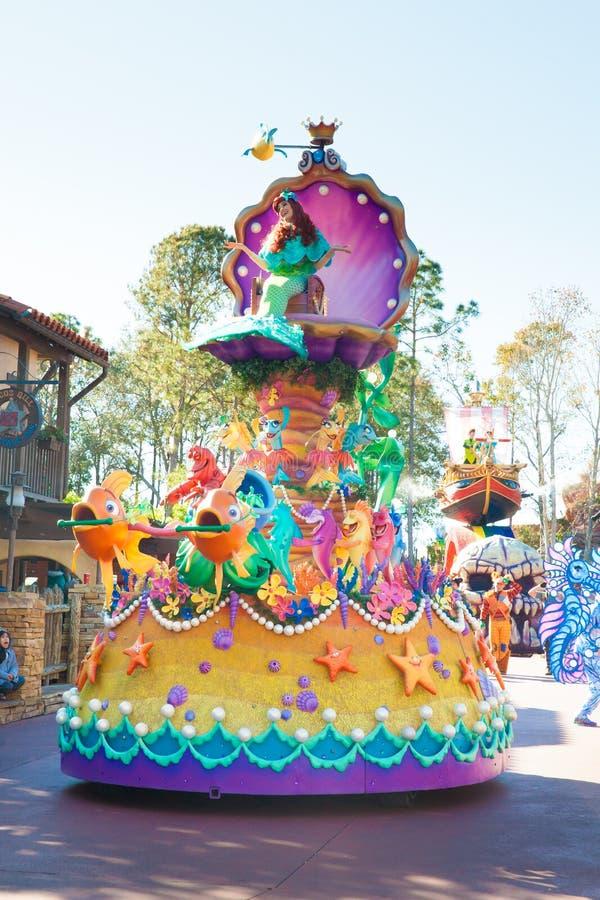 Gli anfitrioni in costumi variopinti che guidano su un galleggiante che partecipano a DisneyWorld sfoggiano immagini stock libere da diritti