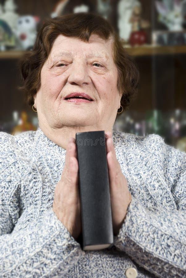 Gli anziani che pregano e tengono una bibbia fotografia stock