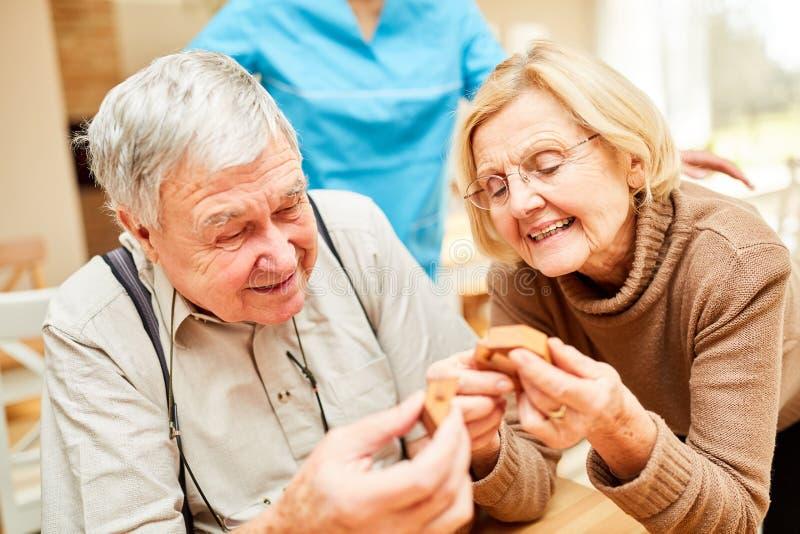 Gli anziani con demenza giocano un puzzle immagini stock