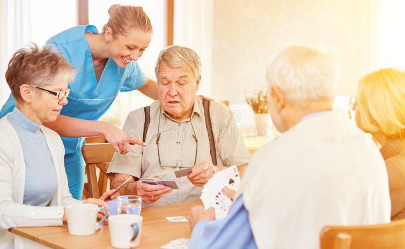 Gli anziani giocano le carte nel loro tempo libero a casa di riposo fotografia stock libera da diritti