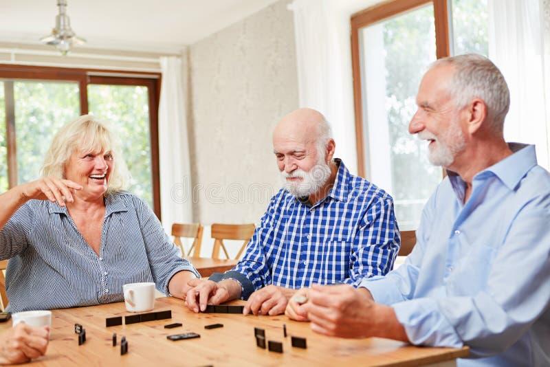 Gli anziani pensionati giocano insieme i domino fotografia stock
