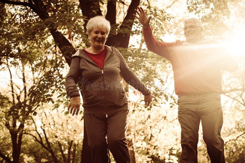 Gli anziani si accoppiano in abbigliamento di sport che godono insieme in nazionale immagini stock libere da diritti