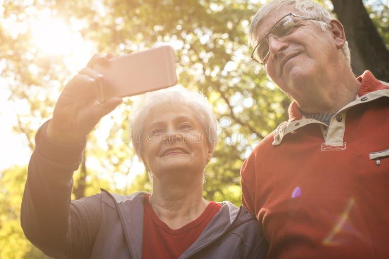 Gli anziani si accoppiano in abbigliamento di sport che prende l'immagine di auto dentro fotografie stock libere da diritti