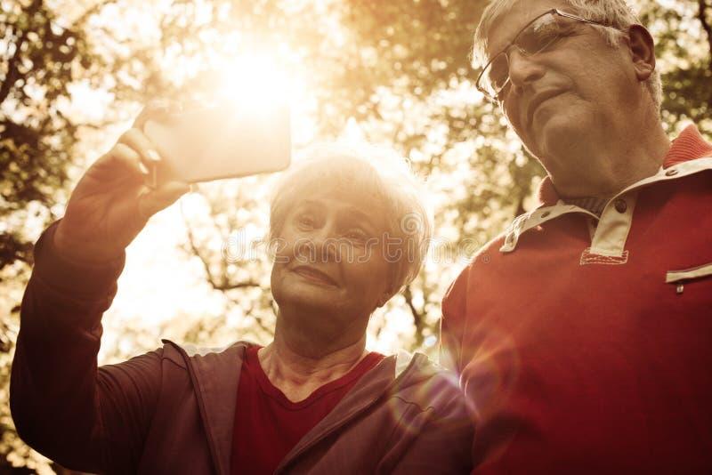 Gli anziani si accoppiano in abbigliamento di sport che prende l'immagine i di auto immagine stock