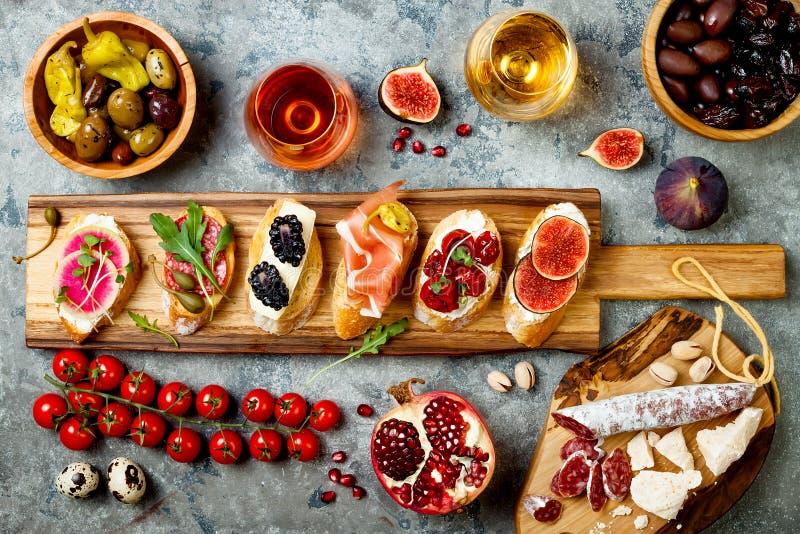 Gli aperitivi presentano con gli spuntini ed il vino italiani dei antipasti in vetri Brushetta o tapas spagnoli tradizionali aute immagini stock