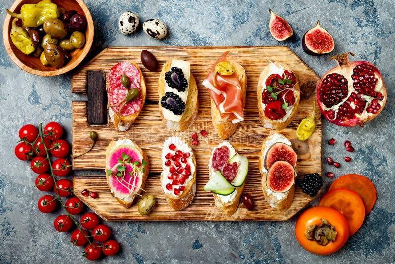 Gli aperitivi presentano con gli spuntini italiani dei antipasti Brushetta o tapas spagnoli tradizionali autentici messi fotografie stock libere da diritti