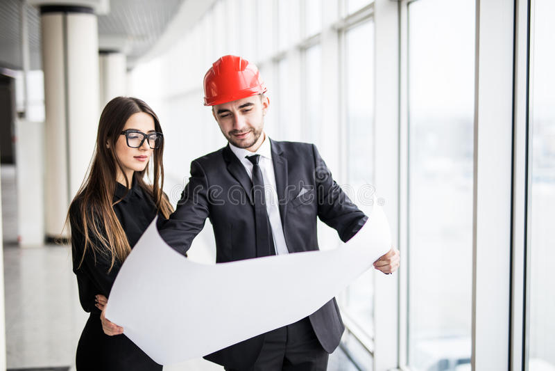 Gli architetti dell'uomo d'affari esaminano l'architetto di carta della donna di affari di piano in ufficio per discutere i proge fotografia stock