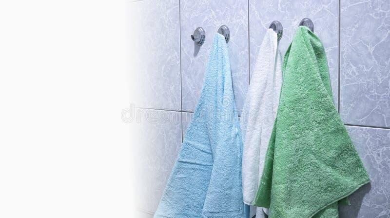 Gli asciugamani appendono su uno scaffale del cappotto nel bagno fotografie stock